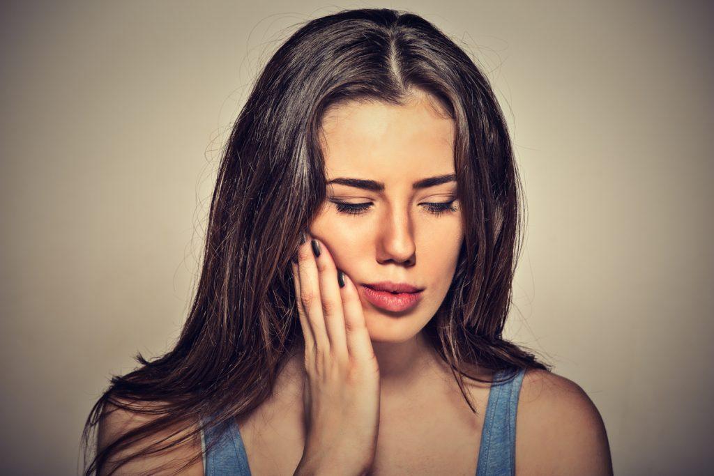 donna che si tocca per il dolore provato da forte sensibilità dentale, possibile causa di pulpite